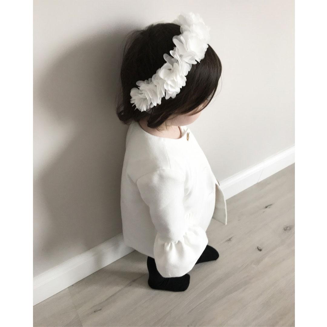 Dziewczynka z białym wiankiem na głowę ubrana w biały płaszczyk